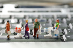有购物车的微型顾客 免版税库存图片