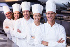 愉快的厨师在商业厨房里一起合作身分 库存图片