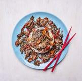低头用米和芝麻,亚洲食谱,在蓝色板材木土气背景顶视图关闭的红色筷子 免版税库存图片