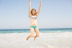 跳跃在海滩的比基尼泳装的无忧无虑的妇女 免版税库存照片