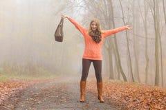 放松在秋天公园的无忧无虑的时尚妇女 免版税图库摄影