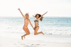 跳跃在海滩的美丽的激动的朋友 免版税库存照片