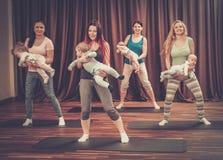 年轻做在地毯的母亲和他们的婴孩瑜伽锻炼在健身演播室 免版税库存图片