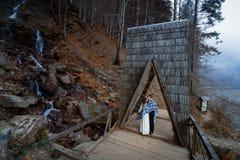婚礼夫妇在木桥软软地亲吻 在山的有薄雾的天 免版税库存图片