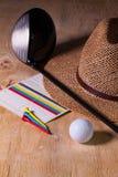 午睡-草帽和高尔夫球司机在一张木书桌上 免版税库存照片