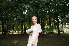 握手和走在公园的新婚佳偶夫妇的全长画象 库存图片