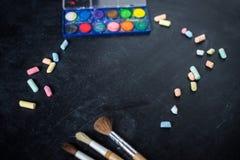 το σχολείο γραφείων απεικόνισης παρέχει το διάνυσμα Κιμωλία διεσπαρμένη και βούρτσες χρωμάτων στον παλαιό μαύρο πίνακα Στοκ Εικόνες