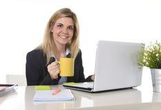 研究有咖啡杯的计算机膝上型计算机的愉快的白肤金发的女商人 库存图片