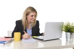 研究便携式计算机的愉快的白种人白肤金发的女商人在现代办公桌 库存图片