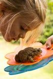 看接近蟾蜍(青蛙)的一个逗人喜爱的女孩 免版税图库摄影