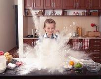 小女孩帮助在一个杂乱厨房里烘烤 免版税图库摄影