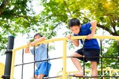 Подъем мальчика на загородке веревочки Стоковая Фотография