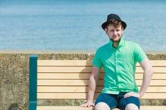 年轻行家人坐长凳在室外的海附近 库存照片
