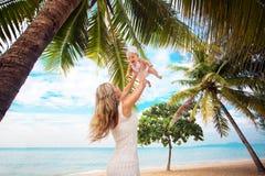 年轻使用在热带海滩的母亲和逗人喜爱的婴孩 免版税库存照片