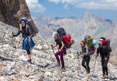 走在离开的岩石地形的小组远足者 库存照片