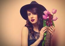 一名年轻美丽的妇女的画象有吉他和郁金香的 免版税库存图片
