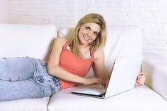 少妇说谎舒适在家庭沙发使用便携式计算机微笑的互联网愉快 库存照片