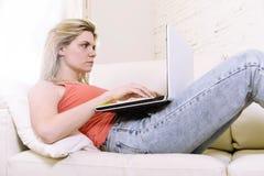 年轻有吸引力金发妇女说谎舒适在家庭沙发使用便携式计算机的互联网 免版税库存照片