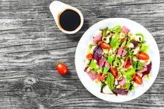 与混杂的莴苣叶子的壳面团可口在白色盘的沙拉,蒜味咸腊肠与坚果,蜂蜜和芝麻籽调味,特写镜头 免版税库存图片