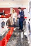 选择洗衣机的夫妇在大型超级市场 库存照片