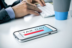 在办公室发短信给在智能手机的税天 免版税库存照片