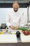 Αρσενικό επαγγελματικό μαγείρεμα αρχιμαγείρων σε μια κουζίνα Στοκ φωτογραφία με δικαίωμα ελεύθερης χρήσης