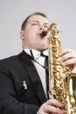 音乐题材和想法 弹萨克斯管的一个白种人男性萨克斯管吹奏者 免版税库存图片