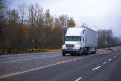 半白色卡车和拖车在秋天路 免版税库存图片