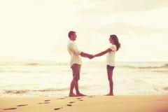在海滩的浪漫夫妇在日落 库存照片