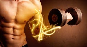 与能量的强健的身体建造者举的重量在二头肌点燃 图库摄影