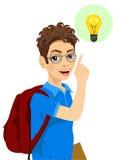 戴眼镜的年轻少年学生男孩指向手指的有的电灯泡想法 库存照片