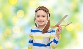 飞行员帽子的愉快的小男孩有飞机的 免版税图库摄影