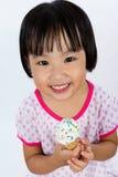 吃冰淇凌的亚裔矮小的中国女孩 免版税图库摄影