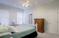 有床和梳妆台的简单的卧室 免版税库存照片