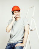 Молодой реальный человек труженика изолированный на белой предпосылке на представлять лестницы усмехаясь, концепция дела Стоковые Фотографии RF