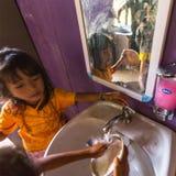 孩子得到食物在午餐时间在学校由项目柬埔寨人孩子关心 免版税库存图片