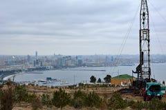 石油钻井船具在巴库,阿塞拜疆的首都,有在城市和里海的看法 免版税库存图片