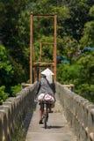 Ινδονησιακή γυναίκα στο παραδοσιακό καπέλο που οδηγά το ποδήλατό της Στοκ φωτογραφία με δικαίωμα ελεύθερης χρήσης