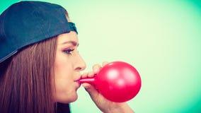 Κορίτσι εφήβων που φυσά το κόκκινο μπαλόνι Στοκ Εικόνα