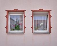 在桃红色墙壁上的两个葡萄酒被构筑的窗口 免版税库存照片