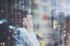 照片妇女佩带的白色衬衣,谈的智能手机和在手上举行经营计划 露天场所顶楼办公室 全景视窗 免版税库存图片
