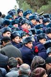 运载红色康乃馨的军校学生在纪念碑在巴库 免版税库存图片