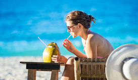 Νέος χυμός καρύδων κατανάλωσης γυναικών χαλαρώνοντας Στοκ Εικόνες