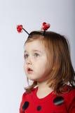 瓢虫服装的小滑稽的女孩 免版税图库摄影