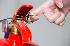 Περίβολος επάνω στον πυροσβεστήρα και το τράβηγμα της καρφίτσας στην κόκκινη δεξαμενή Στοκ Εικόνα