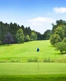 有森林和高尔夫球旗子的田园诗高尔夫球场 免版税库存照片