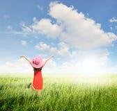 Χαλαρώστε τη γυναίκα στον πράσινους τομέα και το μπλε ουρανό χλόης Στοκ Εικόνες