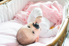 新出生的桃红色摇篮举行黑色安慰者手 免版税图库摄影