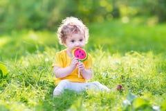 吃西瓜糖果的逗人喜爱的卷曲女婴在公园 免版税库存照片