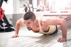 做在健身房的年轻人俯卧撑 库存图片